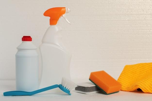 Schoonmaakdiensten voor het schoonmaken van het pand. sponzen, vodden en reinigingsproducten voor sanitair, gootstenen, badkuipen, toiletpotten in flessen op een witte achtergrond