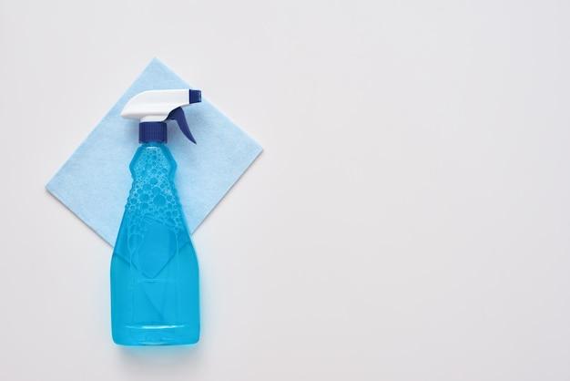 Schoonmaakhulpmiddelen spuitfles en blauwe schonere doek geïsoleerd