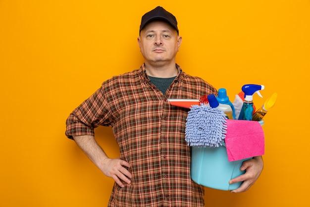 Schoonmaakman in geruit hemd en pet met emmer met schoonmaakgereedschap kijkend naar camera met serieuze zelfverzekerde uitdrukking over oranje achtergrond