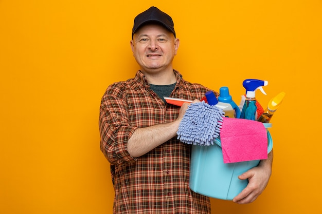 Schoonmaakman in geruit hemd en pet met emmer met schoonmaakhulpmiddelen die met een glimlach op het gezicht blij en positief kijken