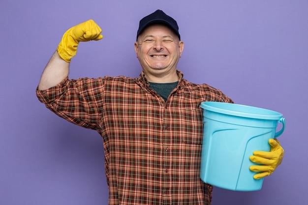 Schoonmaakman in geruit hemd en pet met rubberen handschoenen die een emmer vasthoudt, blij en opgewonden als een winnaar die over een paarse achtergrond staat