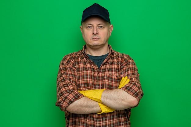 Schoonmaakman in geruit hemd en pet met rubberen handschoenen en kijkend met een serieus gezicht met gekruiste armen