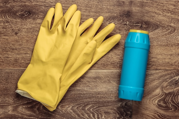 Schoonmaakmiddelen op de vloer. handschoenen, fles. bovenaanzicht. plat leggen