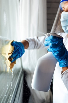 Schoonmaakpersoneel dat het huis desinfecteert tegen virussen, draagt een transparant beschermend masker