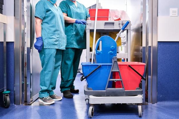 Schoonmaakpersoneel naast een schoonmaakkar in een ziekenhuis