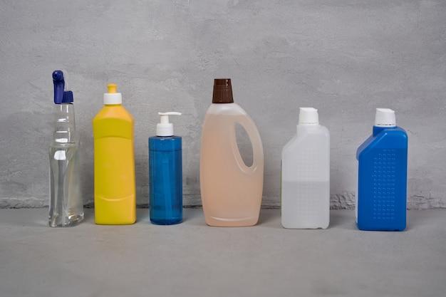 Schoonmaakproducten. kleurrijke plastic flessen met verschillende wasmiddelen die op een rij op de vloer staan tegen een grijze muur. huishoudelijk werk, schoonmaakdiensten en desinfectie van het huis, huishouden