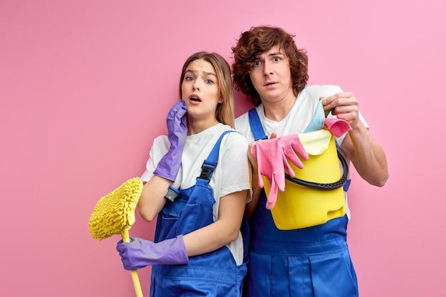 Schoonmaakproducten voor het schoonmaken van verrast man en vrouw in overall en rubberen handschoenen kijken camera geïsoleerd
