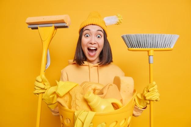 Schoonmaakservice huishoudelijk werk en huishouden concept. positieve aziatische vrouw houdt dweil vast en bezem geeft om nieuw huis, doet huishoudelijke taken nonchalant gekleed geïsoleerd over gele studio-achtergrond