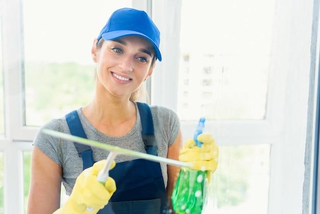 Schoonmaakservice met professionele apparatuur tijdens het werk. professiona tapijt stomerij, sofa stomerij, raam- en vloer wassen. vrouwen in uniform, overall en rubberen handschoenen.