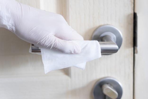 Schoonmaakster afvegende deurknop met antibacterieel desinfectiedoekje in huis voor veiligheid, infectie van het covid-19 virus, besmetting, ziektekiemen, bacteriën voor een goede hygiëne.