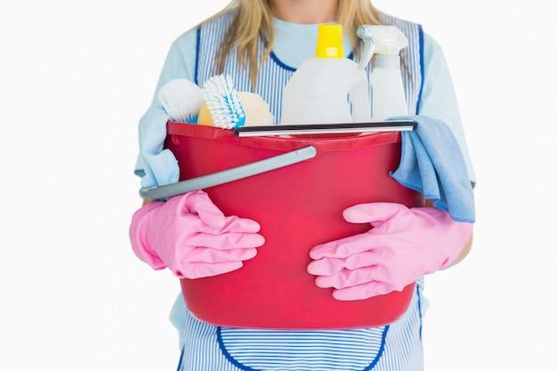 Schoonmaakster die een emmer schoonmakende levering houdt