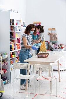 Schoonmaakster die een winkel reinigt terwijl mensen kleding kopen. Premium Foto