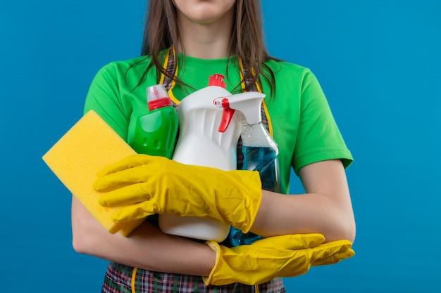 Schoonmaakster die eenvormig in handschoenen draagt die schoonmakende hulpmiddelen op geïsoleerde blauwe muur houden