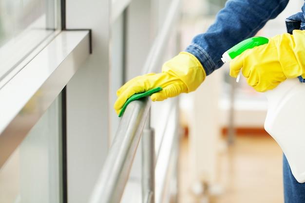 Schoonmaakster doet de schoonmaak op kantoor met een natte doek.