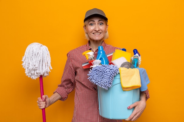 Schoonmaakster in geruit hemd en pet met dweil en emmer met schoonmaakgereedschap die er vrolijk vrolijk en positief uitziet