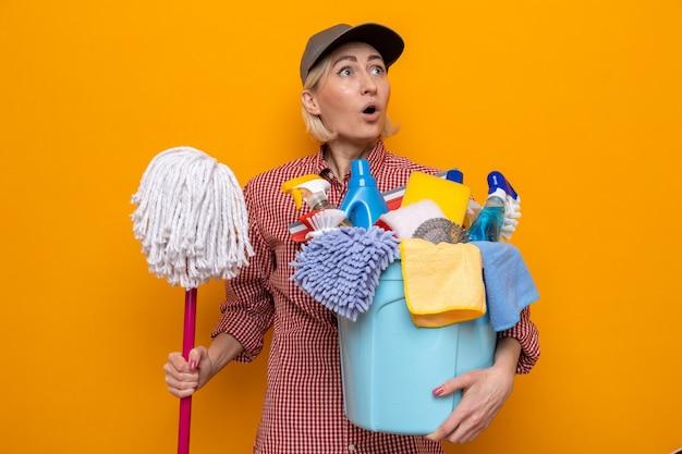 Schoonmaakster in geruit hemd en pet met dweil en emmer met schoonmaakhulpmiddelen die verbaasd en verrast opkijken