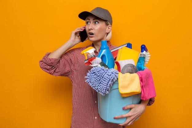 Schoonmaakster in geruit hemd en pet met emmer met schoonmaakgereedschap die verbaasd kijkt terwijl ze op een mobiele telefoon praat die over een oranje achtergrond staat