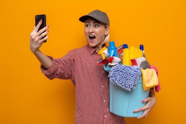 Schoonmaakster in geruit hemd en pet met emmer met schoonmaakgereedschap en kijkt verbaasd en opgewonden naar haar mobiele telefoon