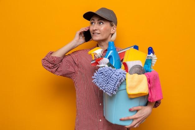 Schoonmaakster in geruit hemd en pet met emmer met schoonmaakgereedschap glimlachend zelfverzekerd terwijl ze op mobiele telefoon praat