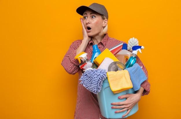 Schoonmaakster in geruit hemd en pet met emmer met schoonmaakgereedschap opzij kijkend verbaasd en verrast over oranje achtergrond orange