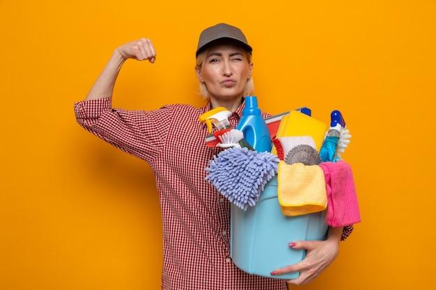 Schoonmaakster in geruit hemd en pet met emmer met schoonmaakhulpmiddelen kijkend naar camera gelukkig en zelfverzekerd die vuist opheft als een winnaar die over oranje achtergrond staat