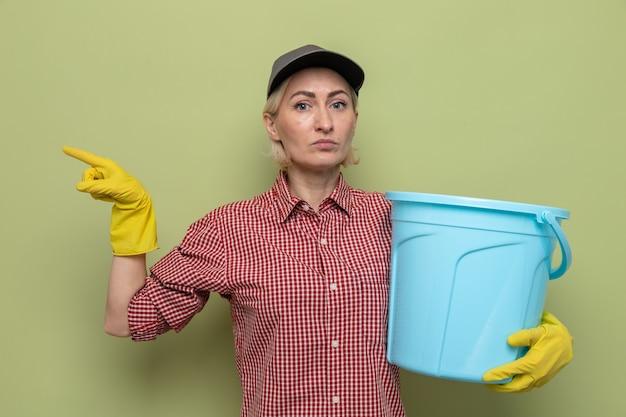 Schoonmaakster in geruit hemd en pet met rubberen handschoenen die een emmer vasthoudt en kijkt met een serieus gezicht wijzend met de wijsvinger naar de zijkant