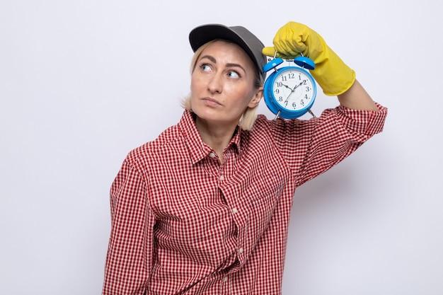 Schoonmaakster in geruit hemd en pet met rubberen handschoenen die een wekker vasthoudt en met een serieus gezicht opkijkt