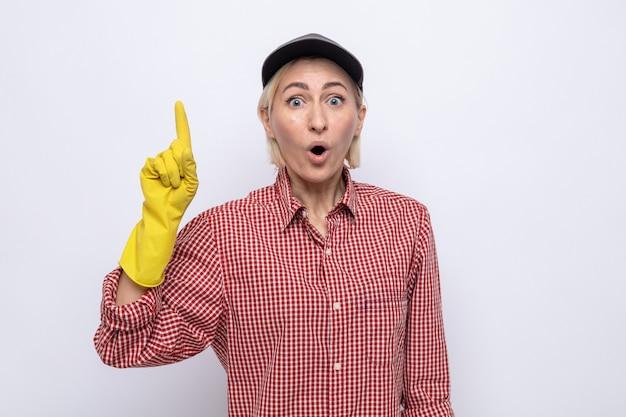 Schoonmaakster in geruit hemd en pet met rubberen handschoenen die er verbaasd uitziet en met wijsvingers omhoog wijst