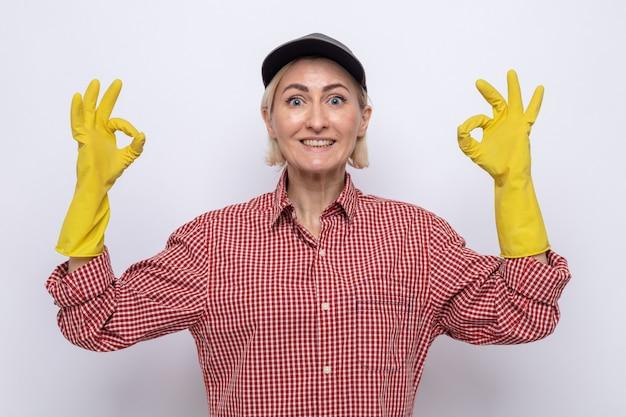 Schoonmaakster in geruit hemd en pet met rubberen handschoenen die naar de camera kijkt en vrolijk lacht met een ok teken dat op een witte achtergrond staat