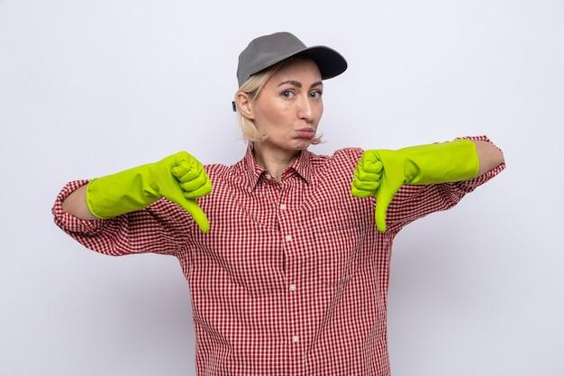 Schoonmaakster in geruit hemd en pet met rubberen handschoenen die naar de camera kijkt, ontevreden met duimen naar beneden staande op een witte achtergrond
