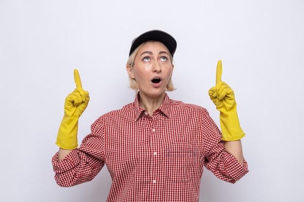Schoonmaakster in geruit hemd en pet met rubberen handschoenen die verbaasd opkijkt en met wijsvingers omhoog wijst