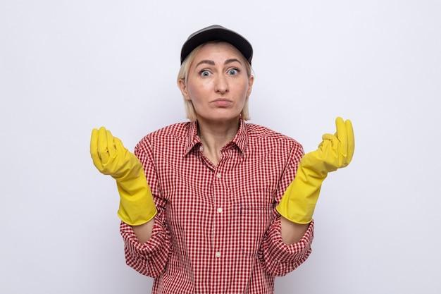 Schoonmaakster in geruit hemd en pet met rubberen handschoenen kijkend naar camera verward wrijven vingers maken geld gebaar staande op witte achtergrond