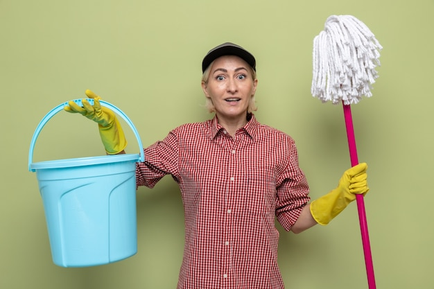 Schoonmaakster in geruit hemd en pet met rubberen handschoenen met emmer en dweil die er vrolijk en positief uitziet