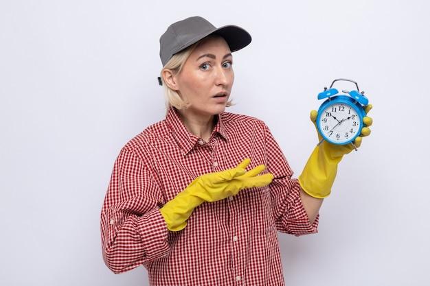 Schoonmaakster in geruit hemd en pet met rubberen handschoenen met wekker die presenteert met de arm van haar hand die er verward en bezorgd uitziet