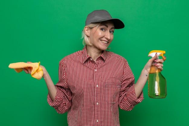 Schoonmaakster in geruit hemd en pet met vod en reinigingsspray die er glimlachend zelfverzekerd uitziet, klaar om schoon te maken