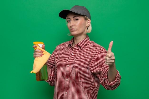 Schoonmaakster in geruit hemd en pet met vod en reinigingsspray, kijkend met zelfverzekerde uitdrukking en duimen omhoog klaar om schoon te maken