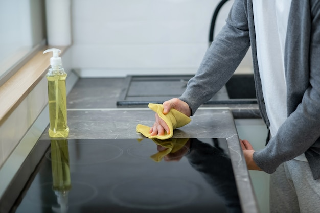 Schoonmaken. close-up foto van een man die het oppervlak van de tafel in de keuken schoonmaakt
