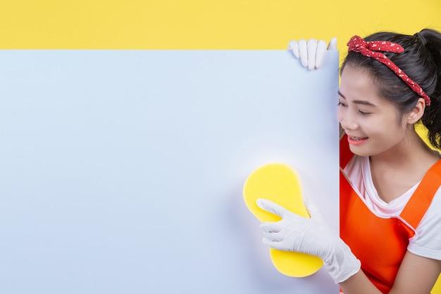 Schoonmaken. een mooie vrouw heeft een wit bord om een advertentiebericht te plaatsen en reinigingsapparatuur op een geel te houden.
