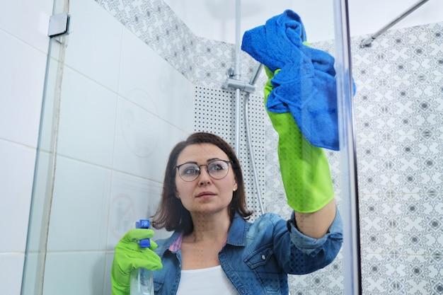 Schoonmaken van badkamer, vrouw wassen en polijsten van doucheglas