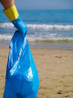 Schoonmaken van het strand van plastic, red de oceaan