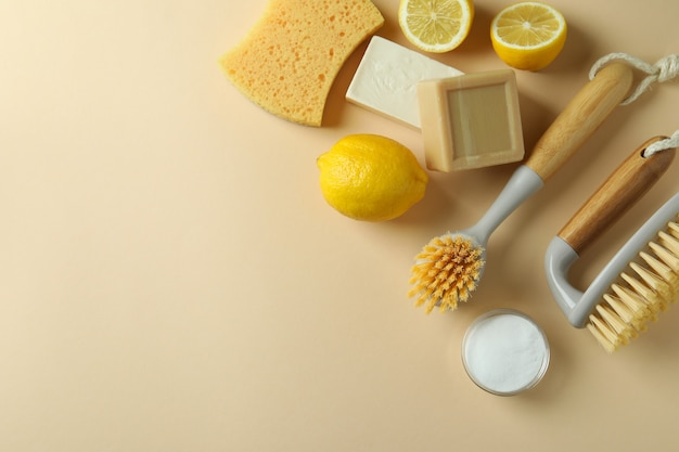 Schoonmakend concept met milieuvriendelijke schoonmakende hulpmiddelen en citroenen op beige geïsoleerde achtergrond