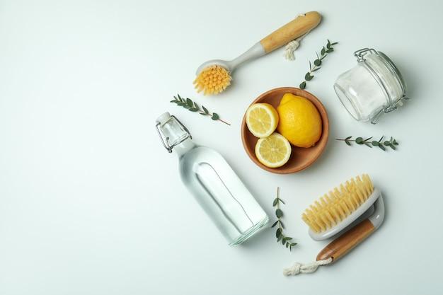Schoonmakend concept met milieuvriendelijke schoonmakende hulpmiddelen en citroenen op wit geïsoleerde achtergrond