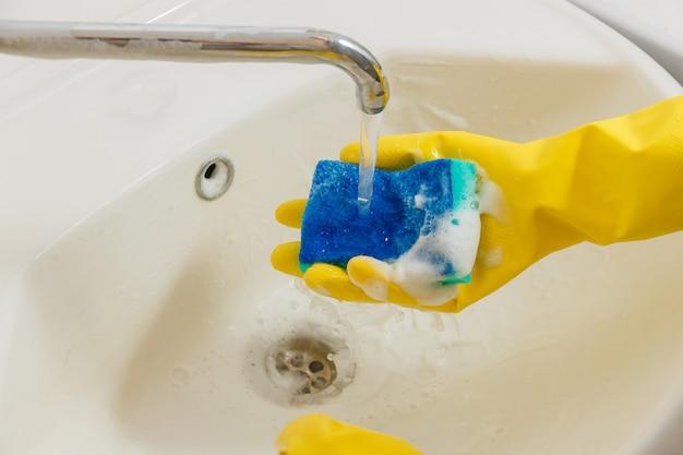 Schoonmakende badkamerskraan met detergens in gele rubberhandschoenen met blauwe spons