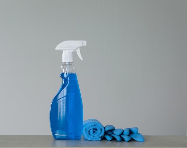 Schoonmakende blauwe nevelfles met plastic automaat, goudsbloemen en doek voor stof op grijze achtergrond