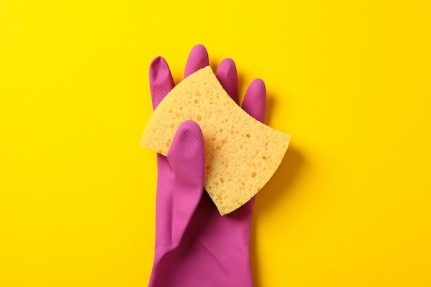 Schoonmakende handschoen en spons op gele achtergrond, ruimte voor tekst