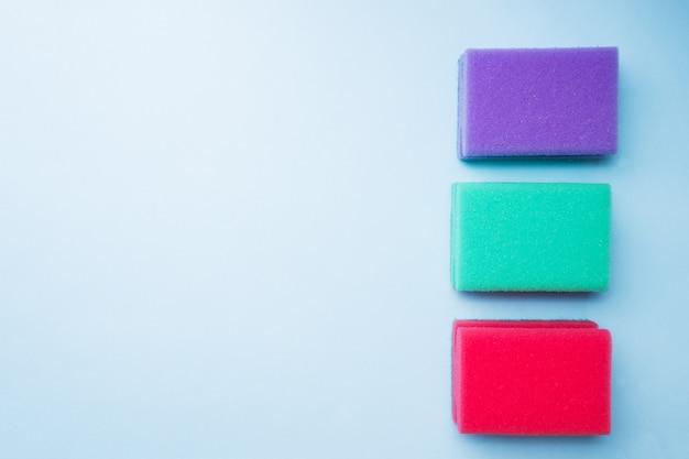 Schoonmakende kleurensponsen en borstels op blauwe achtergrond.