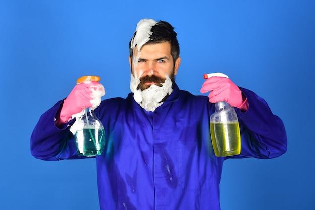 Schoonmakers schoonmaakservice vechten met vuil serieuze bebaarde man met schoonmaakproducten