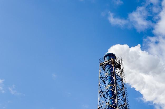 Schoorsteen en stoom op blauwe hemel