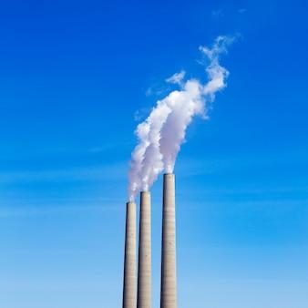 Schoorsteen witte rook drie op een rij op een blauwe hemel