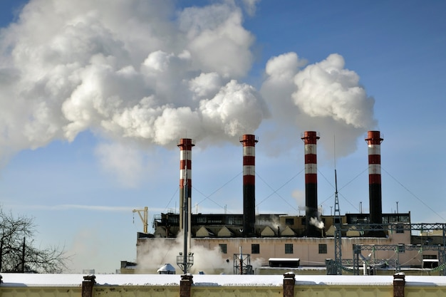 Schoorstenen van de elektriciteitscentrale over blauwe hemelachtergrond